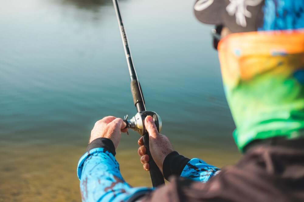 homem utilizando roupas de pesca pescando no rio