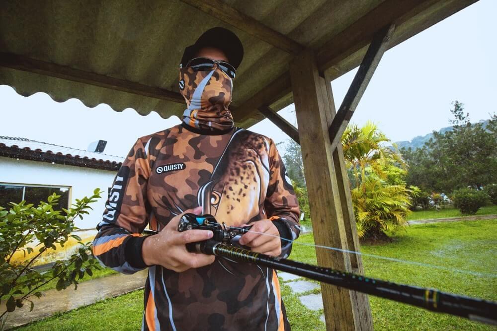homem usando roupas de pesca: boné, máscara, camisa de pesca, óculos, pescando de baixo de um toldo.